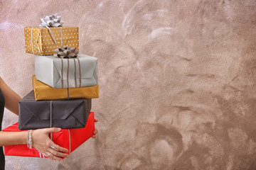 Young woman holding gift boxes on light background