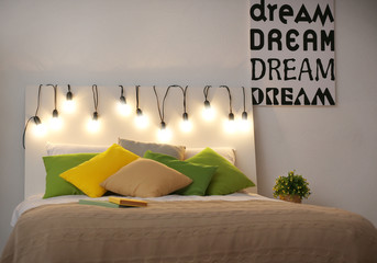 Comfortable double bed decorated with fairy lights at night
