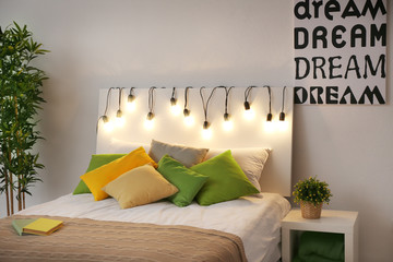 Comfortable double bed in modern stylish interior at night