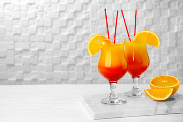 Glasses with cocktail Sex on the Beach against white wall