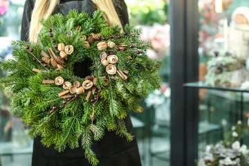 Female florist with Christmas wreath in flower shop