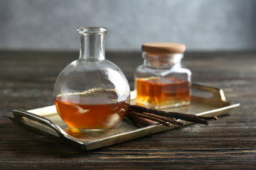 Metal tray with vanilla extract in glassware and sticks on table