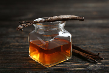 Jar with vanilla extract and sticks on wooden table