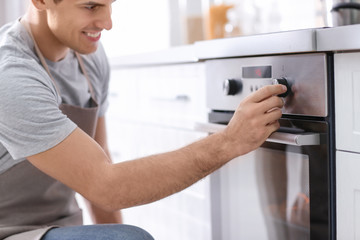 Man adjusting electric oven in kitchen