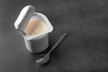 Plastic cup with yogurt on dark background