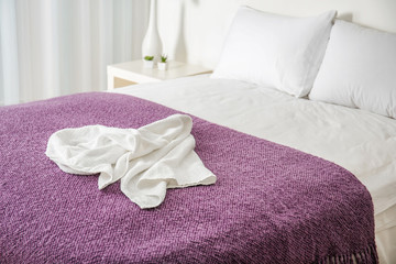 Crumpled towel on comfortable bed in room