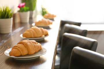 Plates with delicious croissants on wooden table in cafe