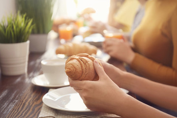 Women eating fresh croissants at table in cafe