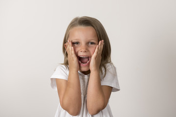 portrait of 7 years old sweet little girl with mouth open screaming surprised or scared holding his head with his small hands isolated on white background