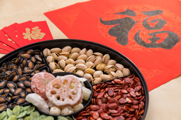 Assorted chinese snack tray with red packet and chinese calligraphy word mean luck