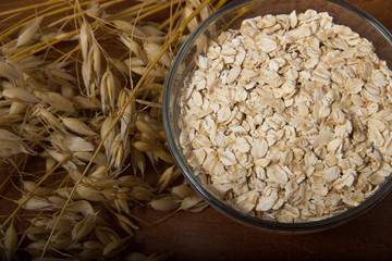 Oat ears stems and oat flakes in a bowl on a dark brown wood background. oatmeal flakes coarse. large-sized flakes. Close up. Useful fiber-rich product. Dietary breakfast from healthy foods