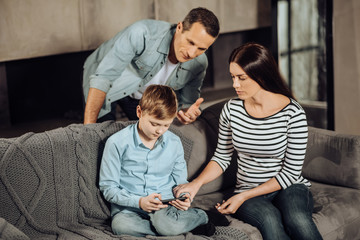 Put it down. Pleasant young parents trying to convince their pre-teen son to stop playing on his phone while the boy being reluctant
