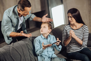 Put down phone. Strict young father reprimanding his son for playing games on the phone too much, the boy being offended, while the mother feeling sorry for the son