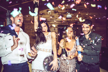 Happy-looking people using party crackers with confetti