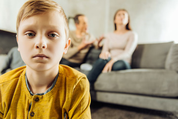 All alone. The focus being on the upset little boy feeling lonely and looking sadly at the camera while his parents sitting on the couch and quarrelling in the background