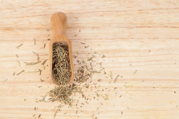 dry rosemary herb in wood scoop on wood background.