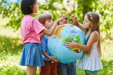 Kinder halten zusammen eine Weltkugel