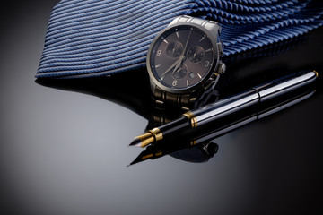 Father's Day or business concept image. Elegant man's watch, fountain pen and blue tie on black gradient background.