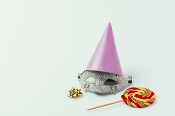 close up view of masquerade mask, party cone and lollipop isolated on grey