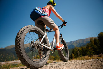 Photo of girl in helmet riding on mountain-bicycle