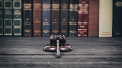 Judge Gavel on a black wooden background in front of a law library.