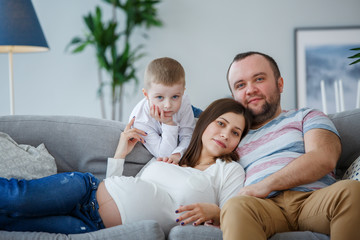 Picture of happy married couple with small son on sofa