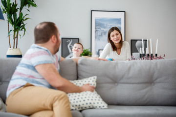 Family image of man sitting with back on couch, son and wife behind sofa