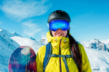 Image of sporty woman in helmet and snowboard against background of snowy hills