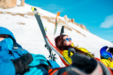 Image of athletes in armchair, skis, sticks in snowy resort