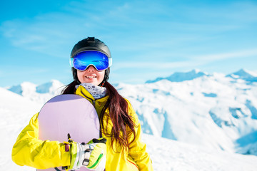 Photo of smiling brunette in helmet and mask with snowboard on background of snowy hills