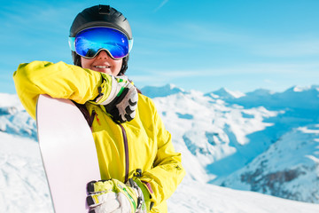 Photo of smiling girl in helmet and mask with snowboard on background of snowy hills