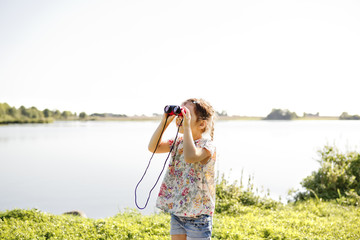 Girl using binoculars in Friseboda, Sweden