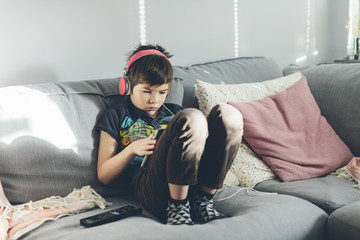 Boy with headphones sitting on sofa