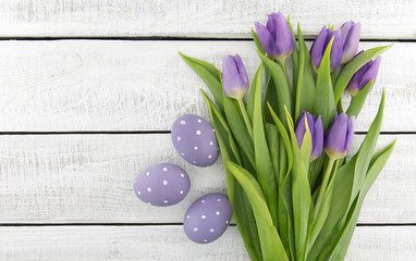 Bouquet of purple(violet) tulips and painted easter eggs on white rustic wooden background with copy space for message. Holiday greeting card. Top view.