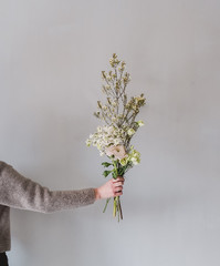 woman holding a little natural bouquet of flowers in her hand