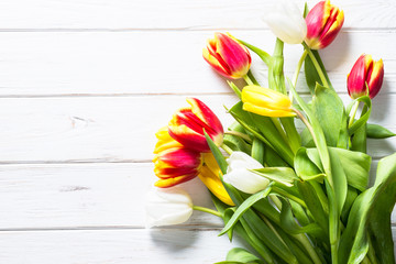 Tulips on white wooden table.