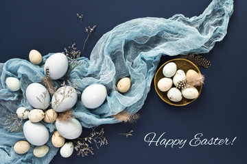 Easter greeting card with eggs and decorations on blue background.