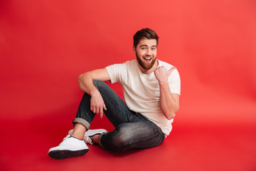 Smiling bearded man sitting on floor pointing.