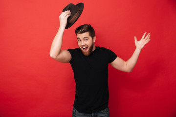 Portrait of amusing bearded man wearing black outfit posing on camera and greeting with taking off hat, isolated over red background Wall mural