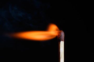 Match with strongly flaring flame beveled on its side on a black background closeup