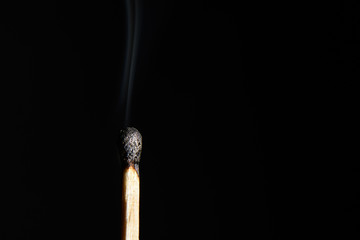 Match with the burned head and heavily steaming up on a black background closeup