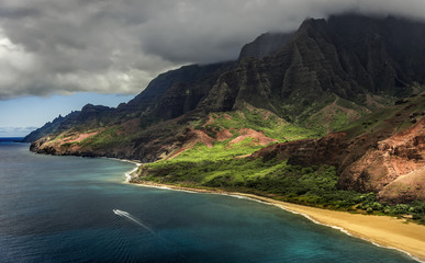 Aerial photograph of Kauai's dramatic NaPali coast with tour boat visible on the ocean.