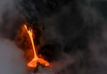 Lava pouring into the Pacific Ocean on the south coast of Hawaii's Big Island.  Photo taken from a boat at sunrise.