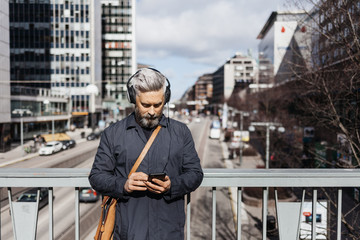 Man with smart phone on street in Stockholm, Sweden