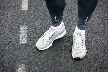 Close up of legs in running shoes standing on asphalt.