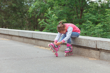 Little girl sitting on parapet and putting on rollers in the park