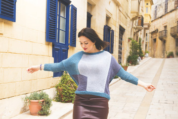 The woman runs on the small street in happy and good mood, towards to spring