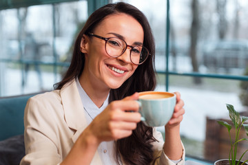 Charming aroma. Jolly cute pretty woman posing on the blurred background while looking at camera and drinking coffee
