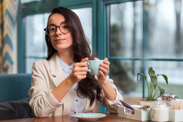 Interesting thing. Concentrated nice pensive woman sitting at the cafe while thinking and holding coffee