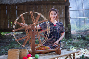 Beautiful Thai women smile in karen suit spinning thread on a bamboo mat in a forest nature local village Thailand